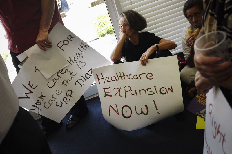 Deborah Dion and other protesters gather in the office of Florida State Rep. Manny Diaz as they protest his stance against the expansion of healthcare coverage on September 20, 2013 in Miami, Florida.
