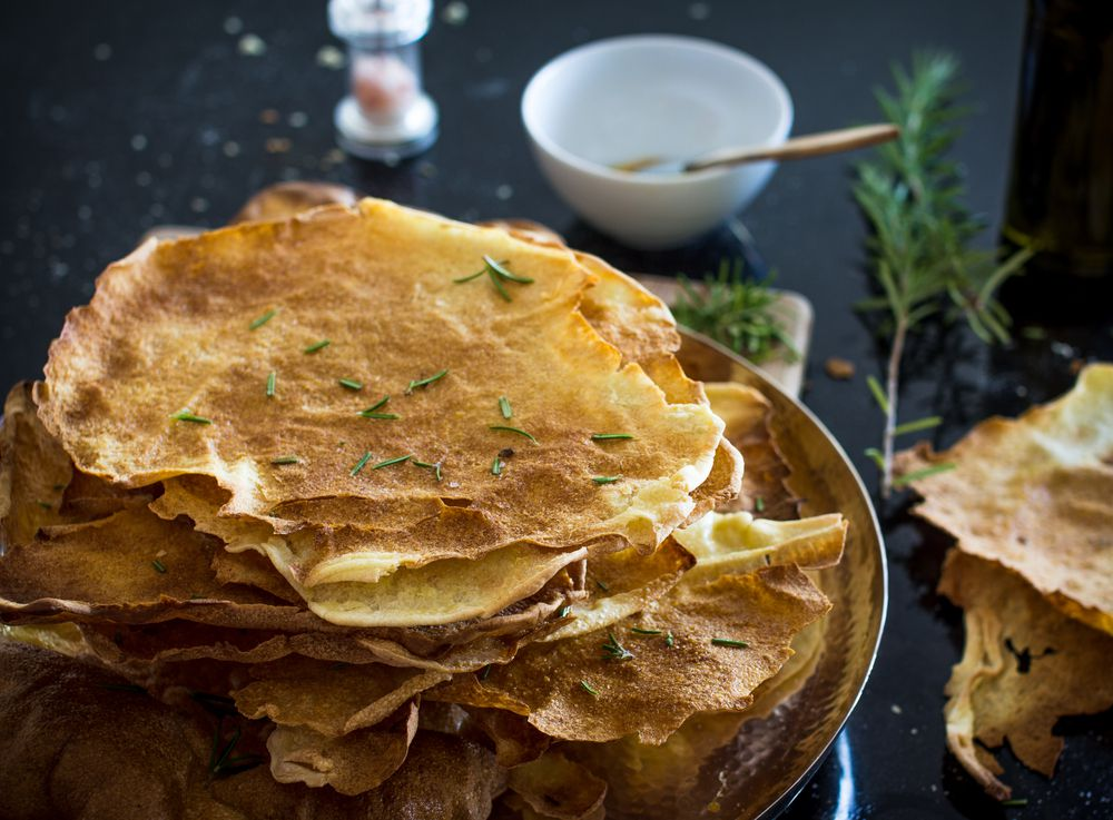 A pile of wafer-thin pane carasau scattered with fresh herbs