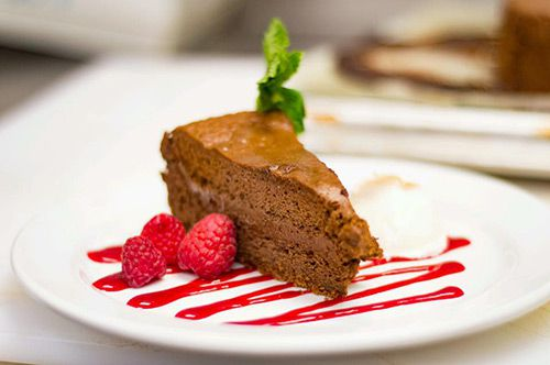 A slice of chocolate cake sits atop a white plate, which is garnished with raspberries and a red, fruity drizzle.