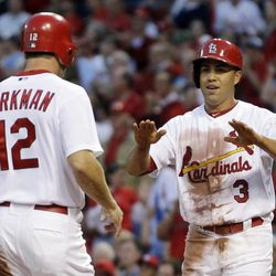 St. Louis Cardinals' Carlos Beltran, right, celebrates with Lance Berkman after both players scored on a double by David Freese during the first inning of a baseball game against the Cincinnati Reds Wednesday, April 18, 2012, in St. Louis.