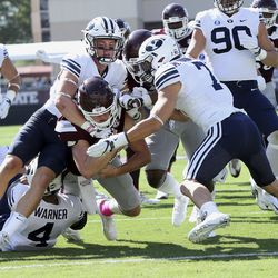 Mississippi State quarterback Nick Fitzgerald, center carries BYU defensive back Zayne Anderson, left, and defensive back Micah Hannemann (7) over the goal line for a touchdown during the first half of an NCAA college football game in Starkville, Miss., Saturday, Oct. 14, 2017. (AP Photo/Jim Lytle)