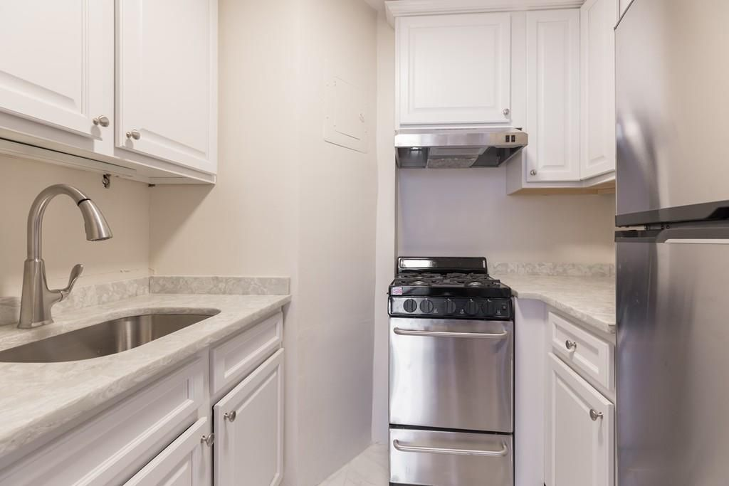 A narrow kitchen with a U-shaped counter.