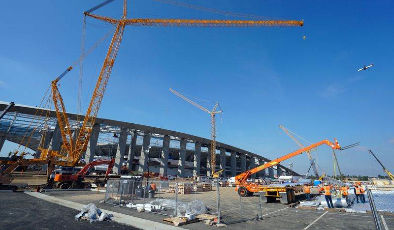 A ground shot of cranes on pavement in front of the stadium.