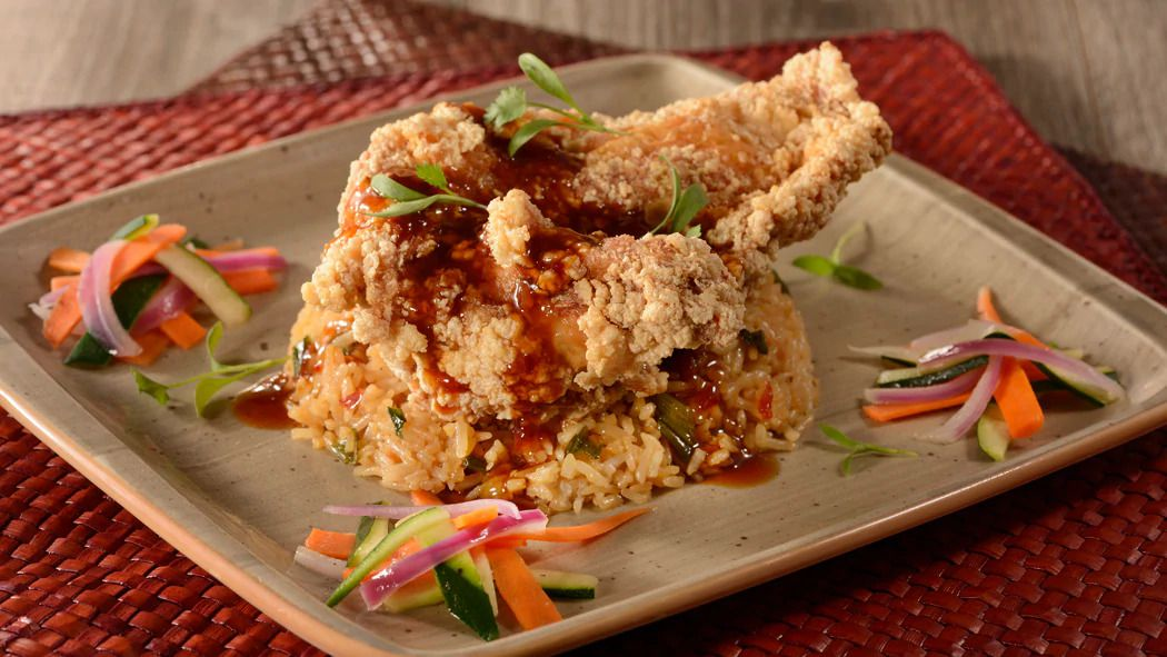 a large hunk of fried chicken drizzled with sauce and sliced vegetables, on a plastic plate set on a wooden tabletop