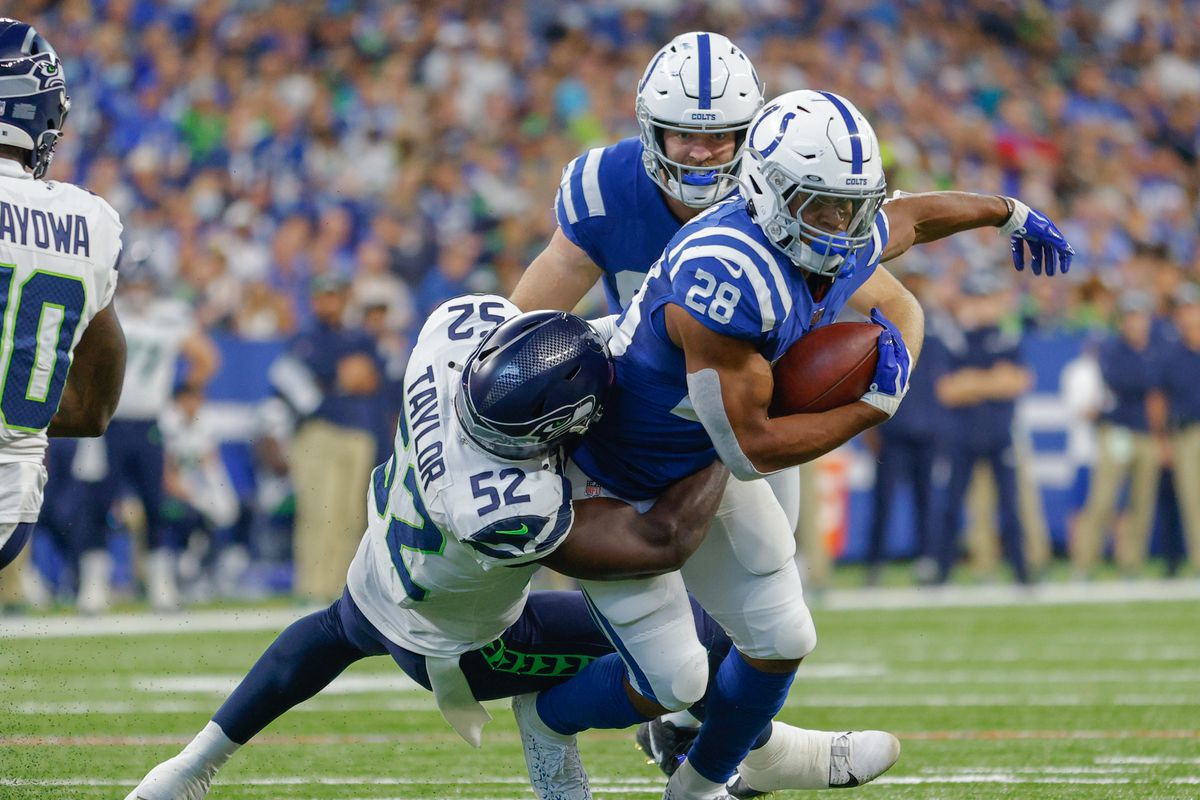 Jonathan Taylor of the Indianapolis Colts runs the ball as Darrell Taylor of the Seattle Seahawks makes the tackle during the game at Lucas Oil Stadium on September 12, 2021 in Indianapolis, Indiana.