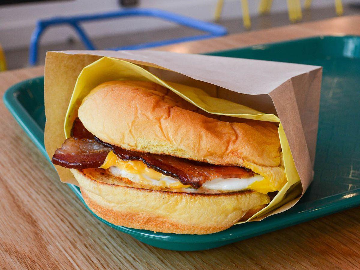 An eggy breakfast sandwich on its side, with bacon.