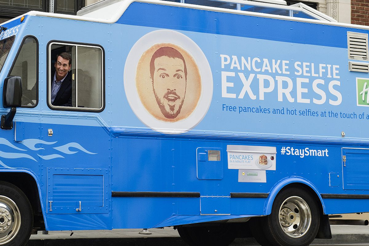 """Rob Riggle, Holiday Inn Express' newly-appointed """"Creative Director and Breakfast Excellence Honcho,"""" driving the Pancake Selfie Express."""