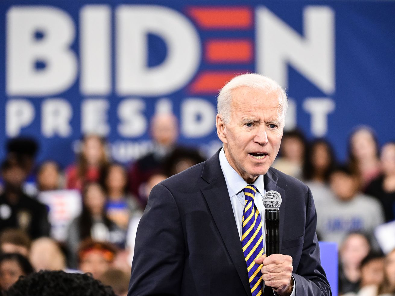 """Presidential candidate Joe Biden speaks onstage at a town hall with a """"Biden for president"""" sign in the background."""