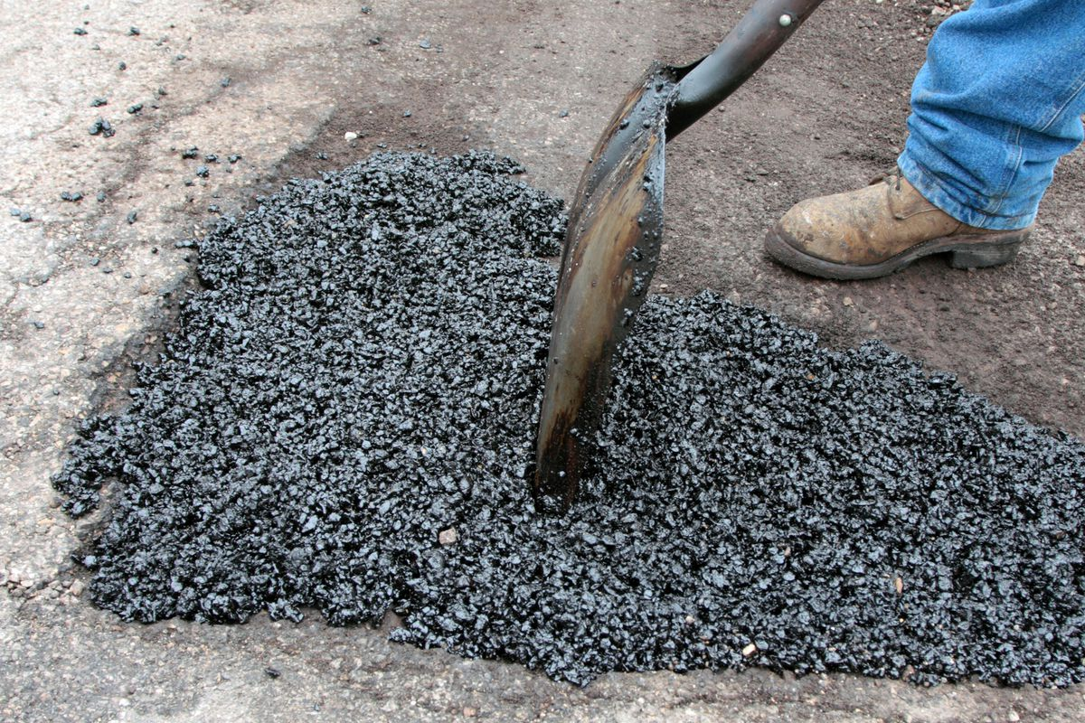 A worker fills a hole with asphalt.