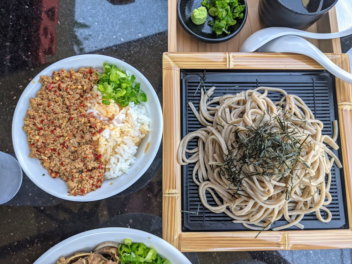 A birds eye view of soba noodles and accoutrements.