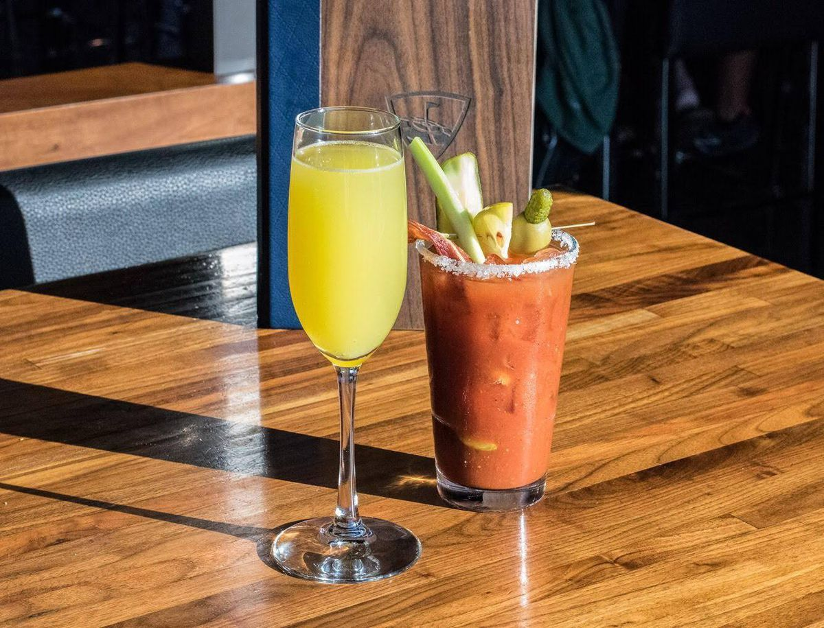 A mimosa and a bloody Mary on a wooden table