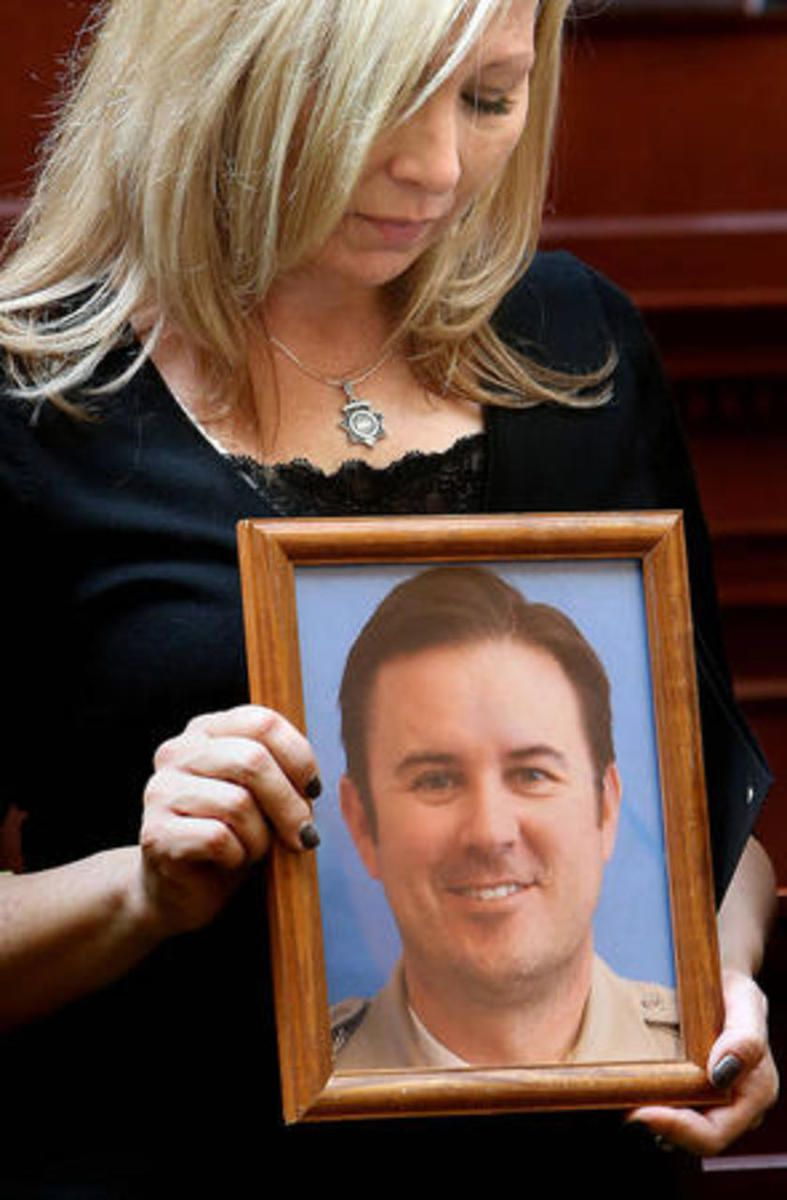 FILE: Nannette Wride holds a photo of her husband, Sgt. Cory Wride, while he is honored at the Capitol on Wednesday, March 12, 2014.