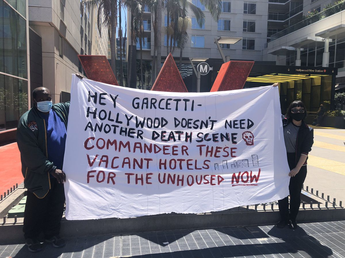 Two people wearing masks standing in front of a W Hotel hold a banner reading 'Hey Garcetti, Hollywood doesn't need another death scene. Commandeer these vacant hotels for the unhoused.'