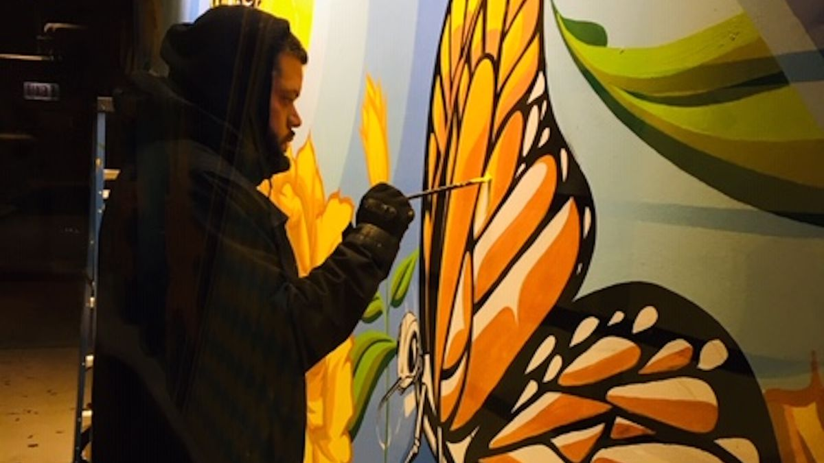 """Miguel Del Real works on the mural """"Community Diligence,"""" painted for an affordable housing development in Albany Park."""
