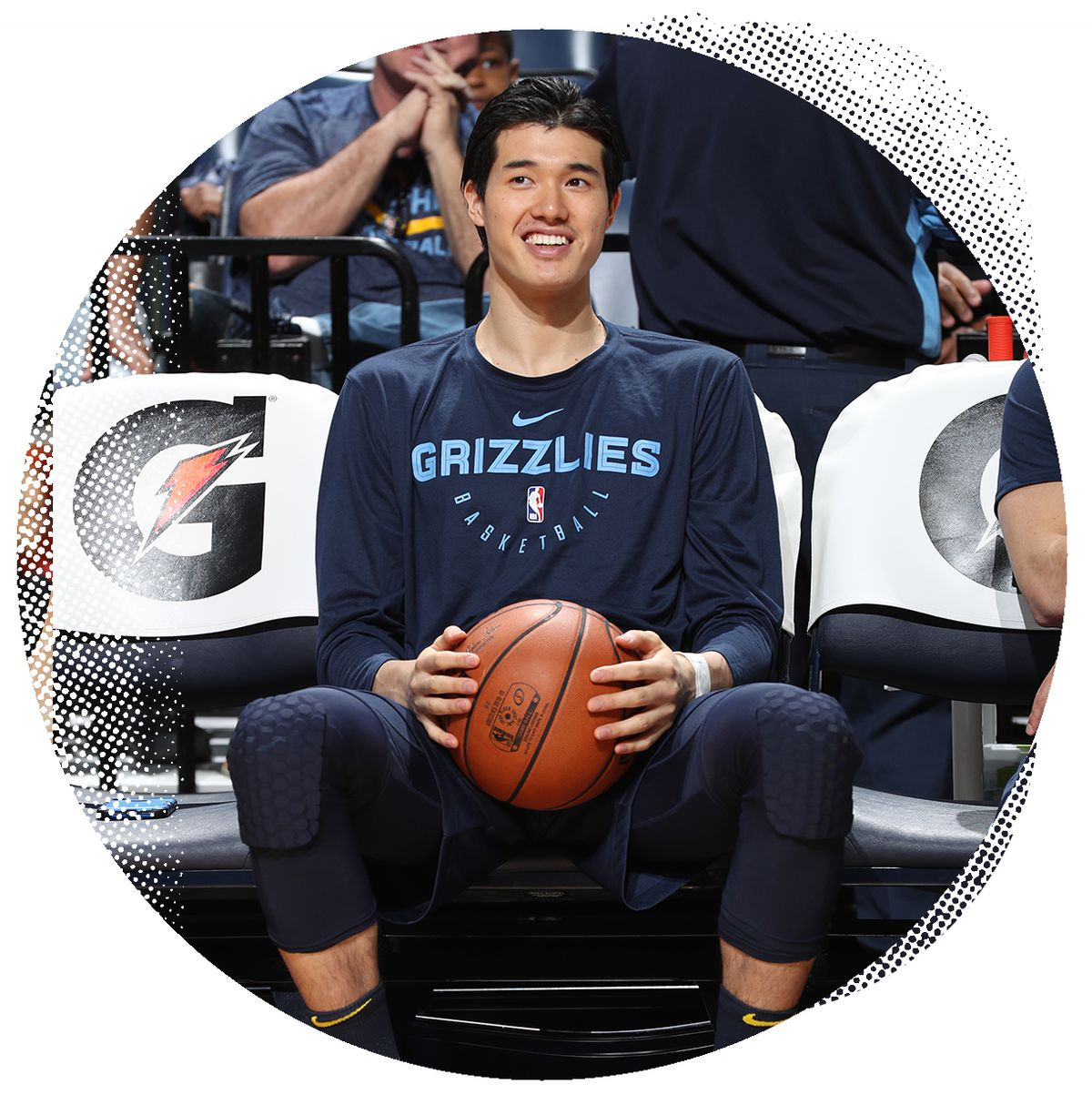 Yuta Watanabe sits in a chair while holding a basketball between his legs.