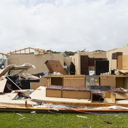 Neighbors inspect a house for occupants in Monroe, La. after an Easter tornado ripped through the town just before noon on Sunday, April 12, 2020.