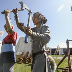Megan Are, right, shows Myles Martin, 11, how to throw an ax during the Utah Renaissance Faire at Thanksgiving Point's Electric Park in Lehi on Friday, Aug. 23, 2019.