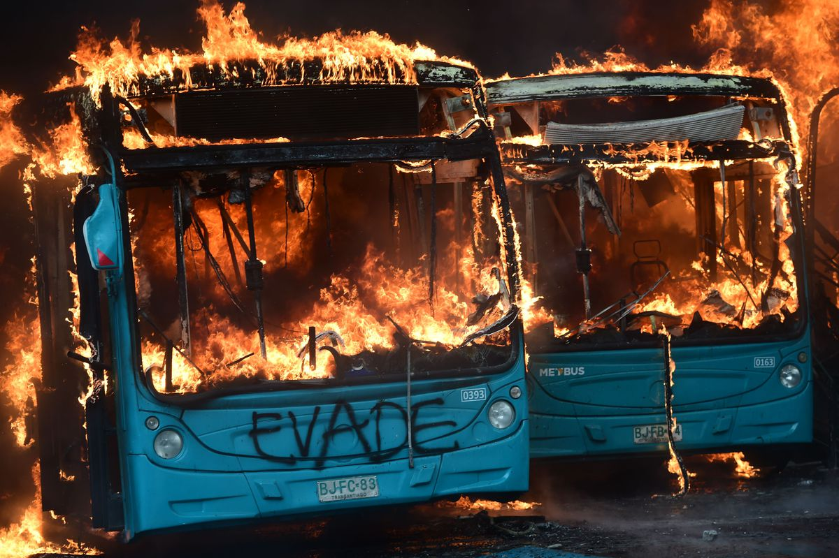 """Two Chilean buses on fire. One has """"Evade"""" spray painted on its front."""