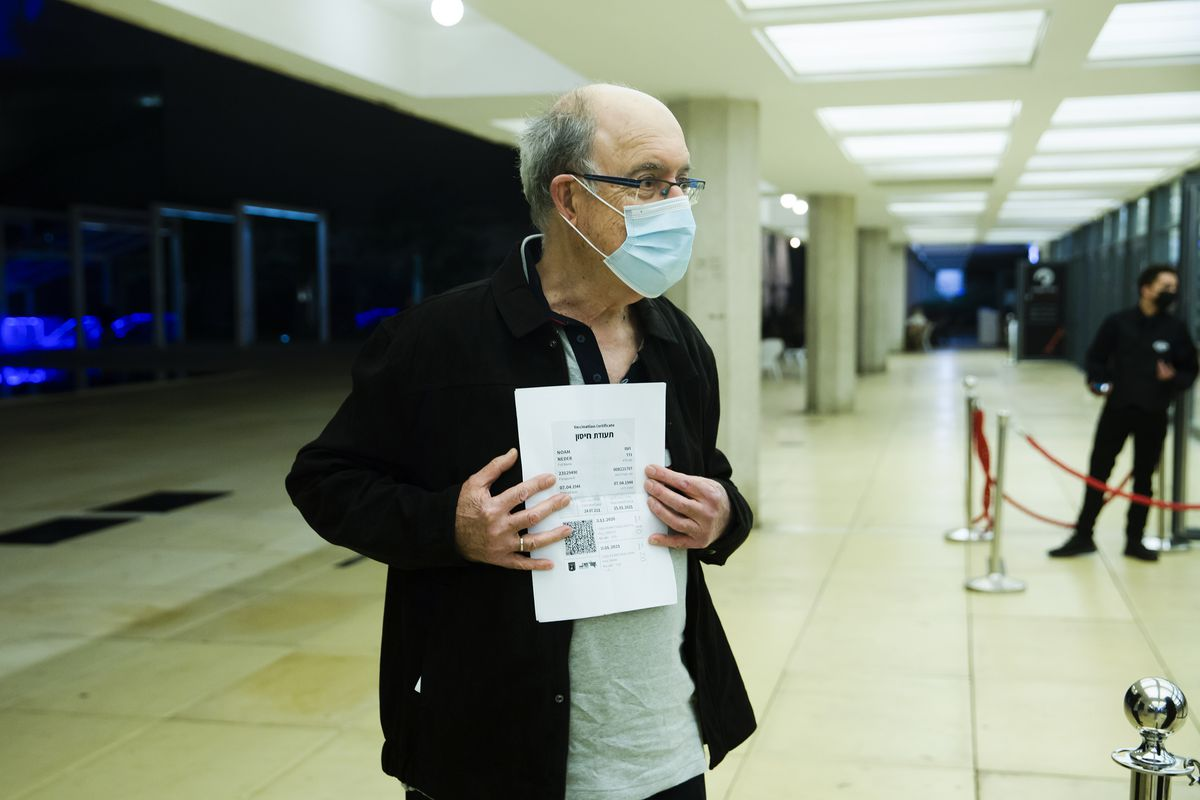 A man presents a Green Pass before entering a musical performance in Tel Aviv, Israel.