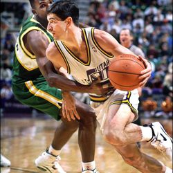 John Stockton is held and fouled by Nate McMillan as he drives to the basket in a Jazz vs. Seattle basketball game in 1994.