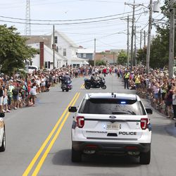 People line the streets of Chincoteague, Va., to get a close look at the wild ponies and foals being walked through town after they swam from nearby Assateague Island during the 94-year-old swim tradition of Pony Penning on Wednesday, July 24, 2019. During the event, the horses navigate through the water for a couple hundred yards, and, after resting, are walked down the streets of town and eventually end up at a carnival where the foals are actioned.