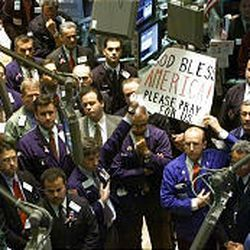 """Traders on the floor of the New York Stock Exchange hold up a sign reading """"God Bless America! Please Pray for U.S."""" during a moment of silence Monday, Sept. 17, 2001 \— just days after the terror attacks. So far it doesn't appear that Hurricane Katrina has had the same impact on investors' psyches as the events of 2001."""
