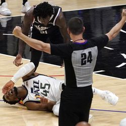 Utah Jazz guard Donovan Mitchell, below, lays on the court after being injured as Los Angeles Clippers guard Patrick Beverley, upper left, check on him and referee Kevin Scott signals during the second half in Game 6 of a second-round NBA basketball playoff series Friday, June 18, 2021, in Los Angeles.