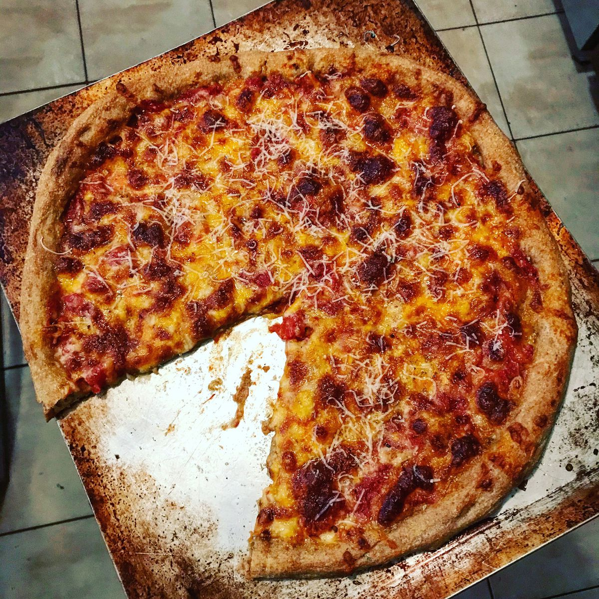 A round cheese pizza sitting atop a burn-stained pizza sheet. One triangle slice is missing