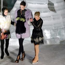 Figure skaters help a model walk off the ice.