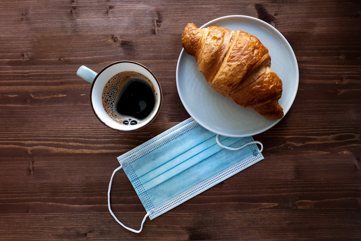 A surgical face mask next to a cup of coffee and a croissant