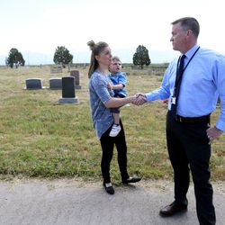 Tessa Stitzer, with her son, Drake, shakes hands with Paul Bergera, Jordan School District staff assistant, at the Bingham City Cemetery in Copperton on Thursday, May 25, 2017. The Jordan School Board has deeded the pioneer cemetery to Copperton Township after 44 years as owner and caretaker. Stitzer serves on the township council and was insistent that the township reassume ownership.