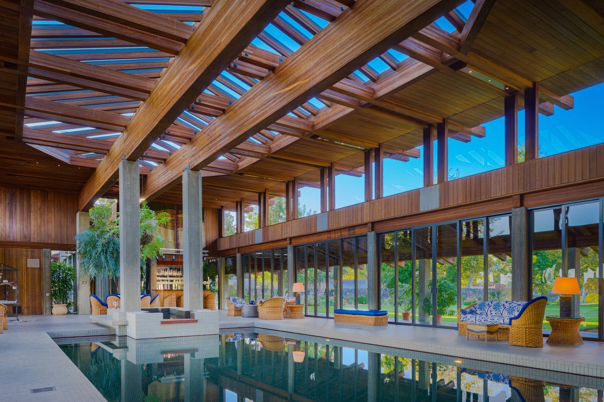 An indoor pool house has a large pool, concrete pillars, and vaulted ceilings.