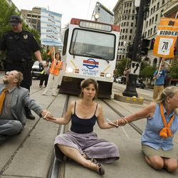Vincent Awolski, Chelsea Satre, and  Julianne Waters  sit across the TRAX line on 400 South and Main Street following the sentencing of Tim DeChristopher on Tuesday, July 26, 2011.