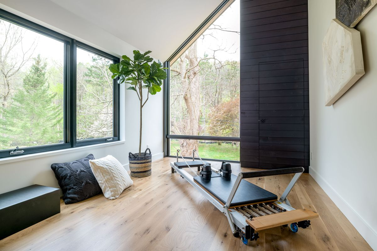 A stained shiplap closet in a workout room with pilates equipment and large windows.