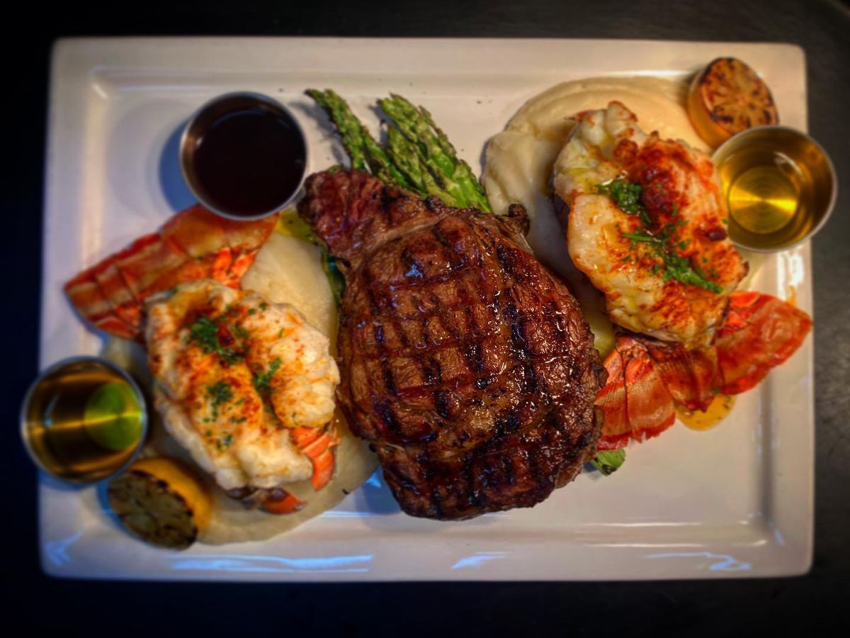 A steak with two lobster tails and asparagus on the side