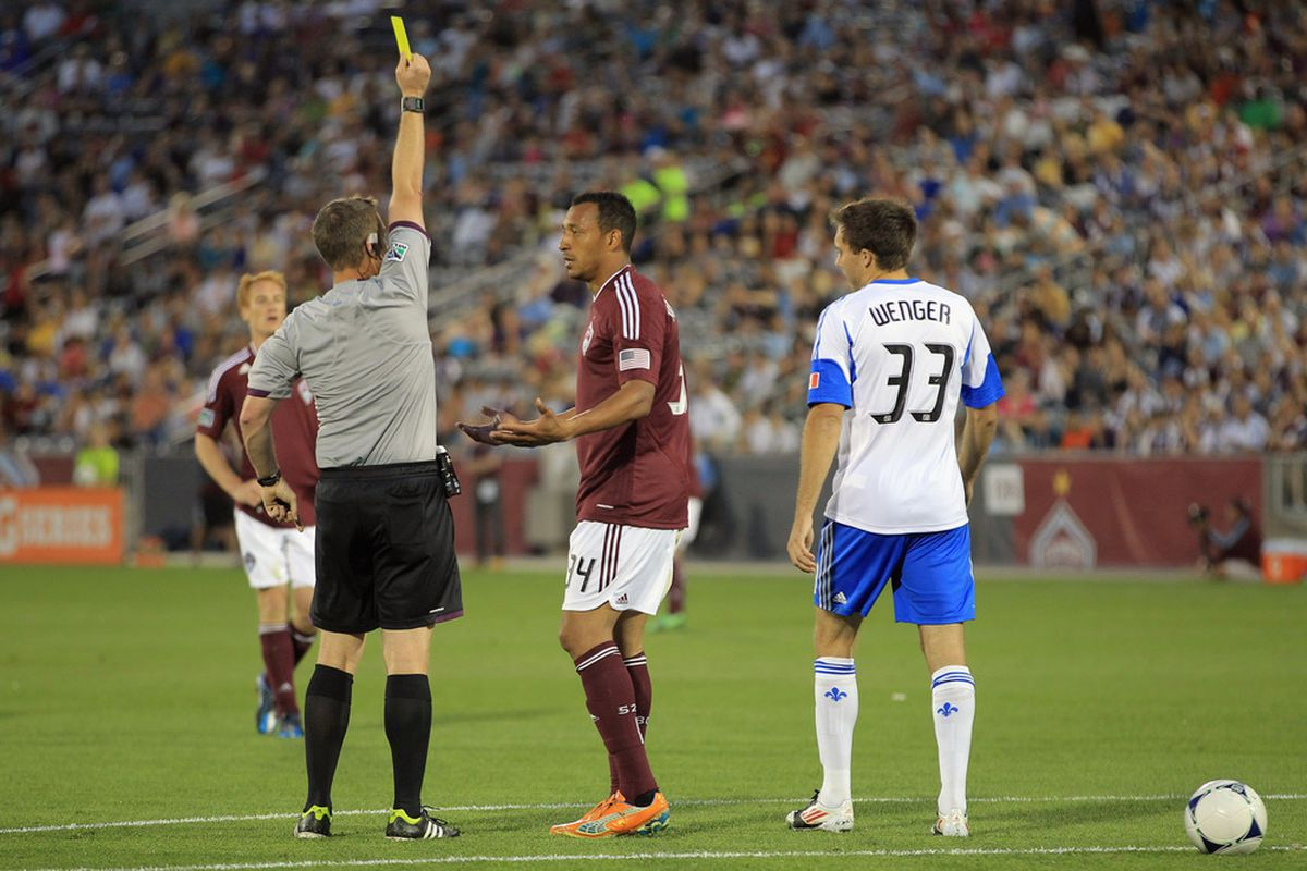 COMMERCE CITY, CO - MAY 26:  Referee Mark Kadlecik delivers a yellow card to Tyrone Marshall #34 of the Colorado Rapids. Marshall tried to reason with the referee that he's not even supposed to BE here today.  (Photo by Doug Pensinger/Getty Images)