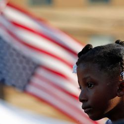 A girl next to an inverted U.S. flag, recognized as a signal of distress. | Jim Young/Getty Images