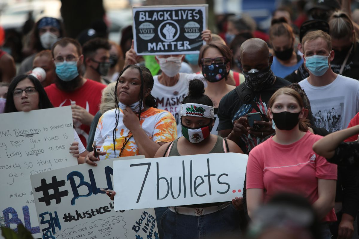 """A crowd of protesters stands in front of the Kenosha County Courthouse with signs that read """"7 bullets"""" and """"Black Lives Matter."""""""
