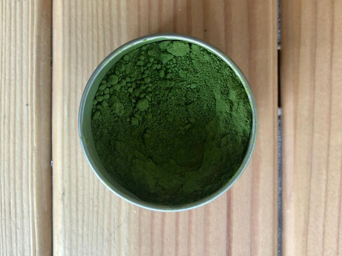 A vibrant grass green powder in a clay bowl on a wooden table