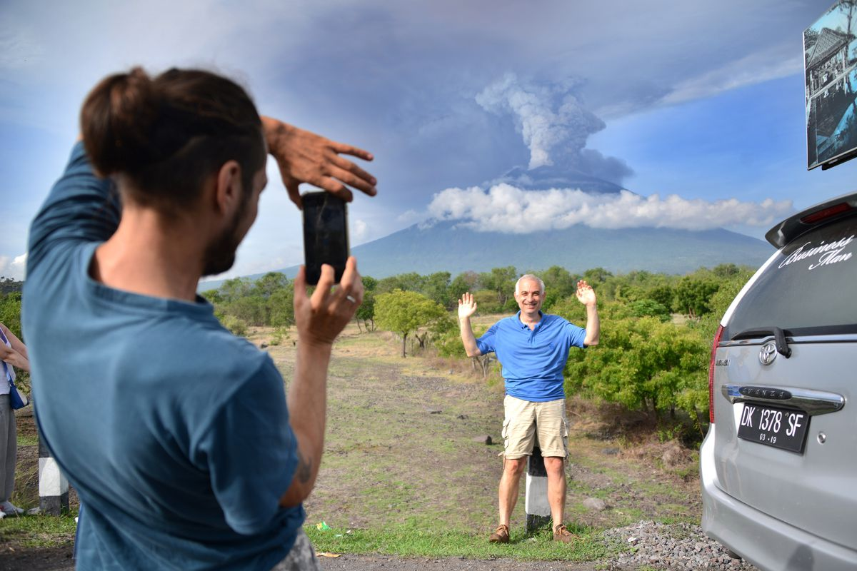 A foreign tourist takes pictures in front of Mount Agung erupting seen from Kubu sub-district in Karangasem Regency, on Indonesia's resort island of Bali on November 27, 2017.