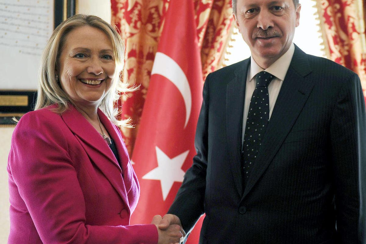 in this photo provided by Turkish Prime Minister's Press Service,  Turkey's Prime Minister Recep Tayyip Erdogan, right, shakes hands with U.S. Secretary of State Hillary Rodham Clinton during a meeting of foreign ministers from dozens of countries gathere