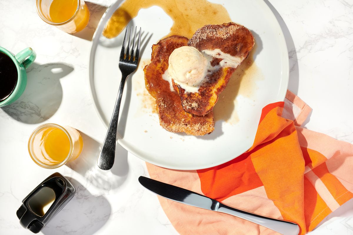 A slice of churro French toast topped with a scoop of ice cream sits next to a fork on a whtie plate. Next to the plate is a cup of coffee, two glasses of orange juice, a knife, and a pink-and-orange napkin.