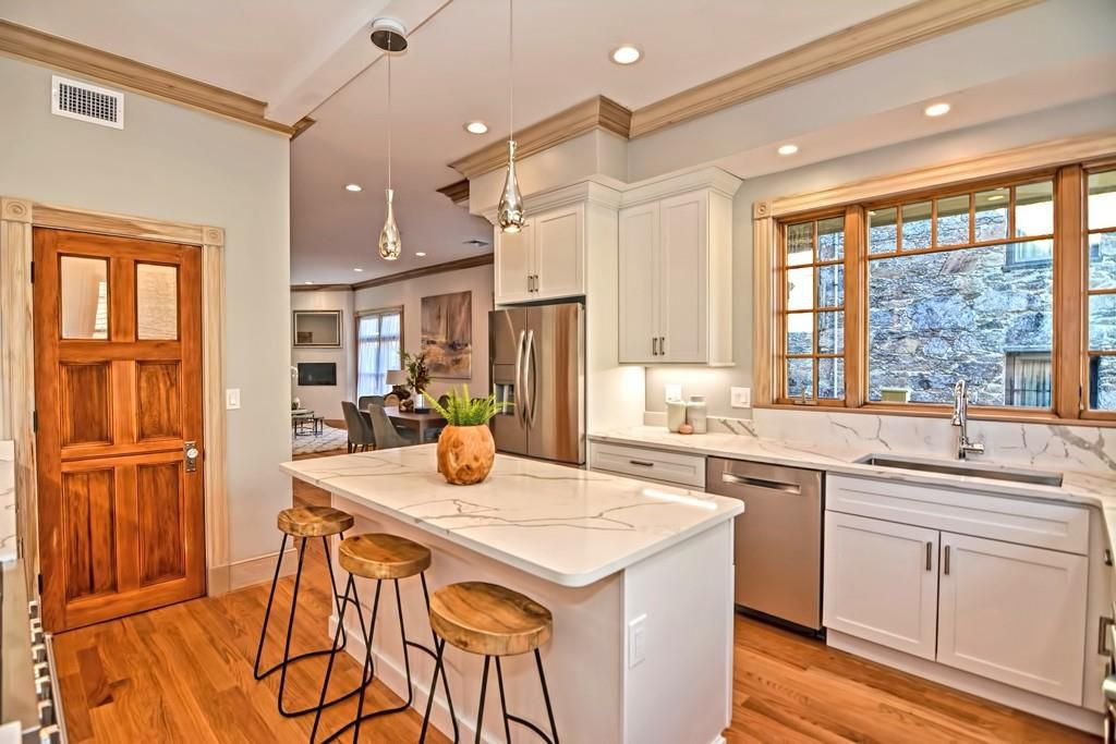 A modern kitchen with a marble island and stools in front of it.