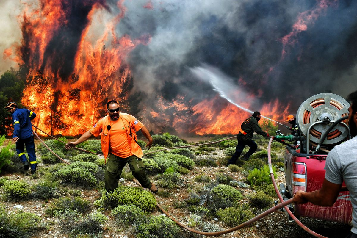 July 24: Firefighters and volunteers try to extinguish flames during a wildfire at the village of Kineta, near Athens, Greece. Raging wildfires killed 74 people including small children in Greece, devouring homes and forests as terrified residents fled to