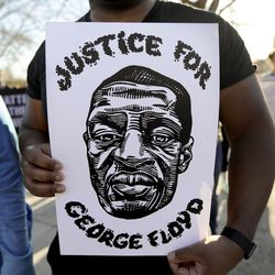 """A man holds a """"Justice for George Floyd"""" sign during a rally in front of the Salt Lake City Public Safety Building after a jury found former Minneapolis police officer Derek Chauvin guilty in the killing of George Floyd on Tuesday, April 20, 2021."""