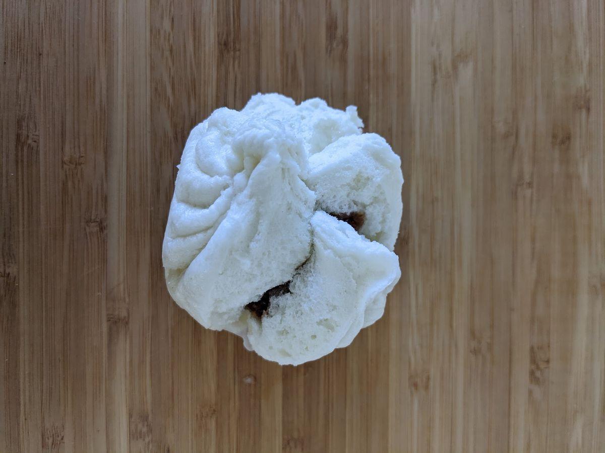 An overhead view of a steamed char siu bao (Chinese BBQ pork bun).