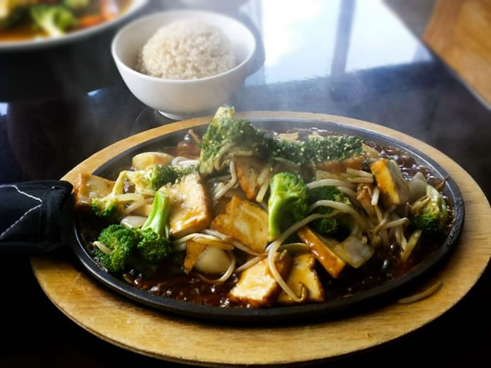 Broccoli, tofu, and more are in a sizzling black plate on a restaurant table