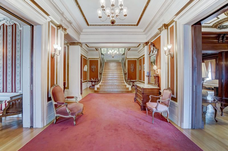 A large hallway features oak floors and red carpet that lead to a double-winged staircase.