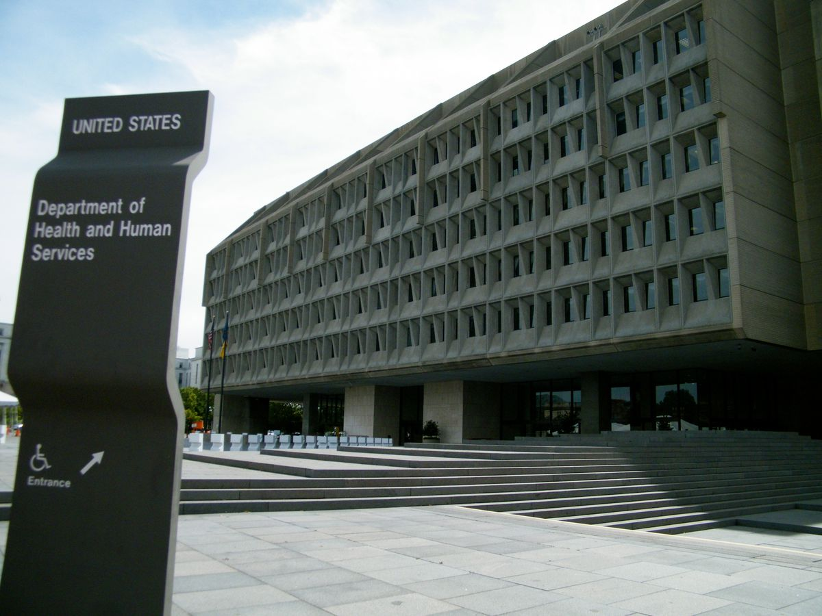 A rectangular building with a concrete vaulted facade with many windows. There is a sign outside of the building that reads: United States Department of Health and Human Services.