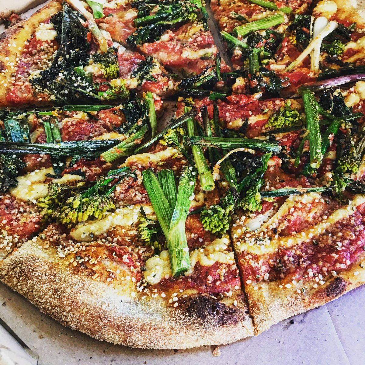 A round sourdough crust pizza topped with broccoli florets, green onions, cheese and marinara